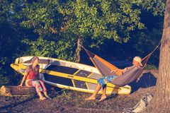 Couple of sup surfers is relaxing in a river camping. Communicates and enjoying life Stock Image