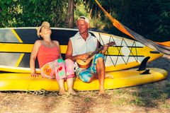 Couple of sup surfers is relaxing in a river camping. Having fun, sings, uses sup like sofa royalty free stock photos