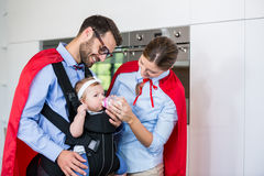 Couple in superhero costume feeding milk to daughter Royalty Free Stock Photography