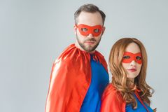 Couple in superhero costumes standing together and looking at camera. Isolated on grey stock image