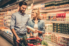 Couple at the supermarket. Beautiful couple is talking and smiling while doing shopping at the supermarket Stock Images