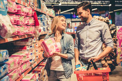 Couple at the supermarket. Beautiful young couple is smiling while doing shopping at the supermarket Stock Photography