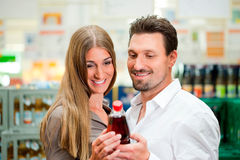 Couple in supermarket buying beverages. Young couple in supermarket buying beverages together Stock Photography