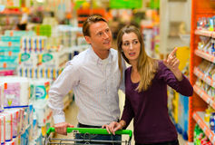 Couple in supermarket with shopping cart Stock Image