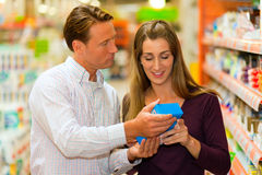 Couple in supermarket with shopping cart Stock Photography