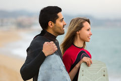 Couple with surf boards on the beach Royalty Free Stock Photos