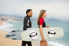Couple with surf boards on the beach Stock Photography