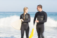 Couple with surfboard walking on the beach Stock Images