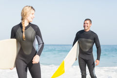 Couple with surfboard walking on the beach Stock Photography