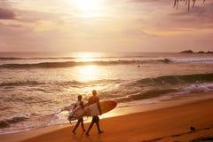 Couple of surfers. Sri Lanka, Hikkaduwa - March 3, 2011: Couple of surfers walks along the beach in Hikkaduva - is the second best surf paradise in Sri Lanka Stock Photography