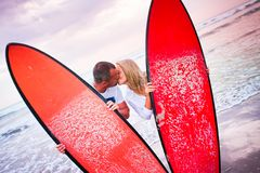 Couple of surfers kissing on coast in Indonesia Stock Images