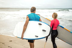 Couple of surfers on ocean`s shore Royalty Free Stock Image