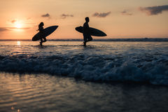 Couple of surfers walking on coastline at sunset stock photo