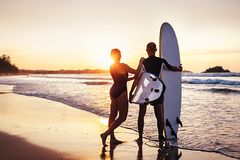 Couple surfers stay on sunset ocean beach Royalty Free Stock Images