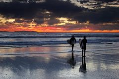 Couple of surfers at sunset. Young female and male surfers on the beach at sunset Royalty Free Stock Image