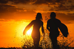 Couple of surfers at sunset Stock Images