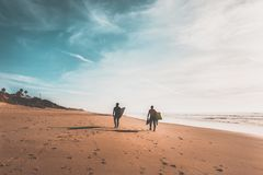 Couple of surfers walking on the beach. Silhouette of two surfing friends walking along the shore carrying their surfboards in search of waves, vintage filter Stock Photography