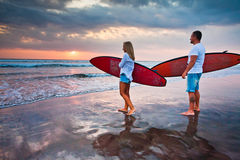Couple of surfers walking on coast in Indonesia Royalty Free Stock Photography