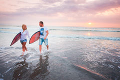 Couple of surfers walking on coast in Indonesia Royalty Free Stock Photos