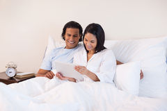 Couple surfing the internet on the bed Stock Images