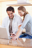 Couple surfing the web in the kitchen Stock Images