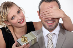 Couple with a surprise gift. Exchange Royalty Free Stock Photo