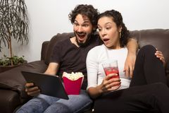 Couple is surprised by the movie. They so sitting on the sofa at. Funny couple is overwhelmed with the movie. Bewildered. Man and women watch series on tablet Stock Image