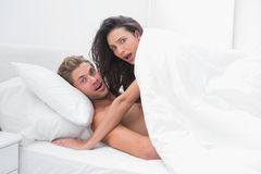 Couple surprised in their bed Royalty Free Stock Photo