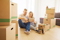 Couple surrounded with moving boxes looking at tablet Stock Photography