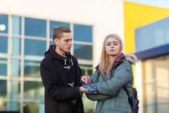 A couple swearing in the street, a guy yelling at a girl from behind a broken mobile phone. A young European couple swearing in the street, a guy yelling at a royalty free stock images