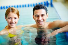 Couple of swimmers. Image of young male and female looking at camera in water Stock Photography