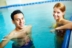 Couple of swimmers. Image of young male and female looking at camera in water Stock Photo