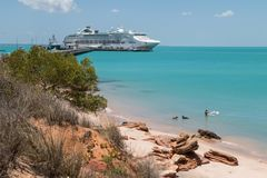 Couple swimming with dogs modern cruise ship tied up to jetty. Stock Image