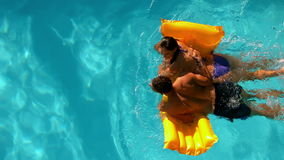 Couple swimming on lilo in pool together stock video footage