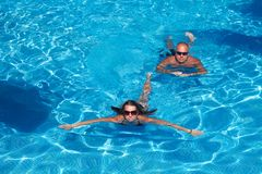 Couple swimming in pool Stock Photos