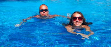 Couple swimming in pool Royalty Free Stock Photos
