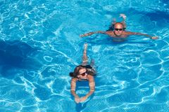 Couple swimming in pool Royalty Free Stock Image
