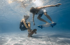Couple in the swimming pool. Man and Woman skateboarding underwater in the swimming pool Stock Photography
