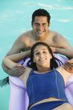 Couple in Swimming Pool woman lying on inflatable raft elevated view portrait. royalty free stock photography