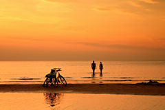 The couple is swimming in the sea at sunset on background of bic Royalty Free Stock Photos