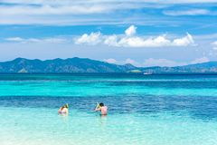 A Couple are Swimming in Two Different Color Sea royalty free stock image