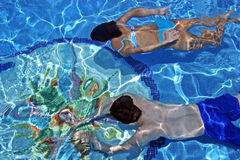 Couple Swimming Underwater In Clear Blue Pool Stock Photos