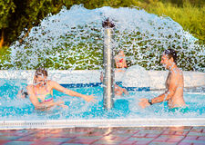 Couple in swimmning pool under splashing fountain. Summer heat. Royalty Free Stock Image