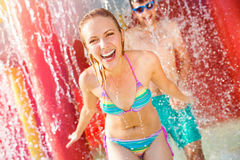 Couple in swimmning suits under splashing fountain. Summer heat. Royalty Free Stock Photo