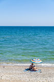 Couple in swimsuit at the beach sitting under umbrella and watching the sea, Crimea, Ukraine Stock Image