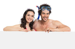 Couple In Swimsuit Holding Sign Royalty Free Stock Photo