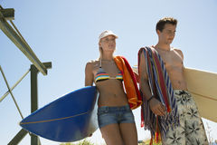 Couple In Swimwear Carrying Surfboards Stock Image