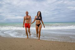 Couple in swimwear coming out from sea in time of surf. Attractive couple at the sea in summer overcast day. Husband and wife in swimwear coming out from sea in royalty free stock photos