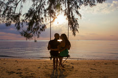 Couple  on a swing against  of  sunset. Couple swinging on a swing against a background of sea sunset Royalty Free Stock Photography