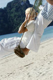 Couple on swing at beach Stock Photos